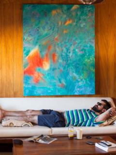 Hombre acostado sobre un sofá y debajo de pintura, ilustra nota de Ecuatoriano compró dibujo por un dólar; se enteró que vale una millonada