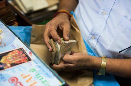 Hombre con fajo de billetes de rupias de India, ilustra nota de video de termitas que se comen los ahorros de toda la vida de granjero indio