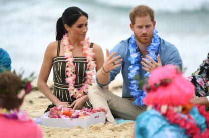 """Príncipe Harry y Meghan Markle con pinta hawaiana en playa de Australia, ilustra nota de Príncipe Harry luce """"americano, parecido a Trump"""": experta en lenguaje corporal"""