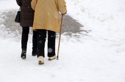 Anciana camina con bastón sobre la nieve con compañía, ilustra nota de Anciana camina 10 km bajo la nieve para recibir vacuna contra el coronavirus