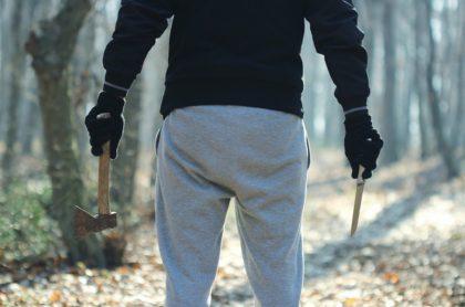 Hombre con guantes negros sostiene hacha y cuchillo en el bosque, ilustra nota de hombre que intenta sacrificar a su hijo como ofrenda a Dios, en Turquía