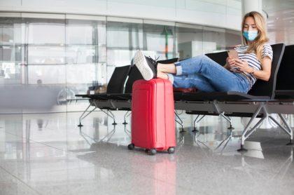 Mujer en aeropuerto con tapabocas, ilustra nota de OMS pide que la vacuna contra el coronavirus no sea requisito para viajar
