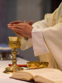 Sacerdote en misa reza sobre hostia, ilustra nota de video de sacerdote se equivoca y pone rap en plena transmisión en vivo de misa