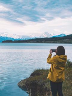 Mujer toma foto con su celular a un lago, ilustra nota de mujer recupera su iPhone funcional meses después de que se le cayó a lago