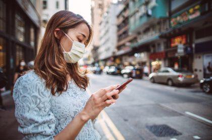 Mujer con tapabocas mira celular en la calle, ilustra nota de mujer que va al médico por lesión de tobillo y descubre que nació como hombre