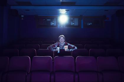 Hombre en cinema, ilustra nota sobre fecha de reapertura de salas de Cine Colombia, el primero de mayo, Día del Trabajo.