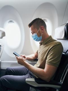 Foto de hombre con tapabocas en un avión, a propósito de medidas de Reino Unico para colombianos
