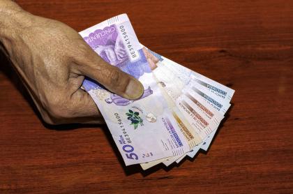 Persona con billetes colombianos ilustra nota sobre personas que podrían empezar a pagar impuesto a la renta