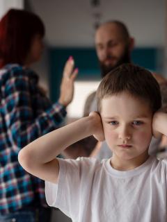 NIño tapándose los oídos mientras papás pelean