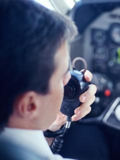 Piloto de avión habla por micrófono, ilustra nota de graban a piloto insultando a ciudad en la que acaba de aterrizar, en EEUU