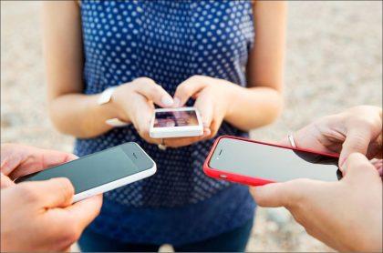 Imagen de jóvenes con celulares, que ilustra la batalla de precios entre operadores móviles luego de llegada de WOM Colombia