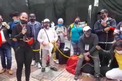 Organizadores de eventos que protestan encadenados en la Plaza de Bolívar de Bogotá