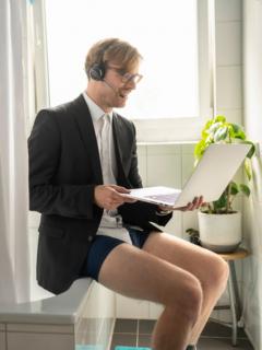Hombre en el baño con computador, ilustra nota de foto de político canadiense que salió completamente desnudo en sesión virtual