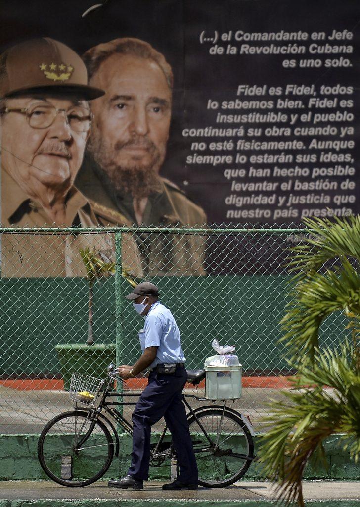 Cubano camina frente a mural de Fidel Castro y Raúl Castro