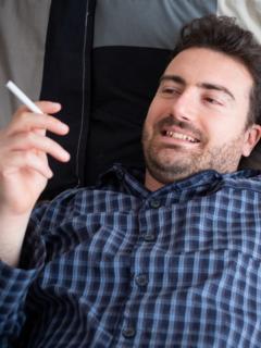 Hombre fumando acostado, ilustra nota de video de pillan a político acostado, fumando y escuchando música en sesión virtual