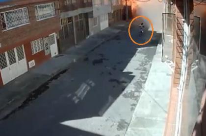 Imagen del momento en que ciclista cruza por el sitio de la explosión en Engativá, Bogotá, en donde una persona murió