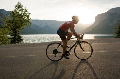 Ciclista monta al lado de un lago, ilustra nota de Ciclista se tragó una abeja, lo picó en la garganta y el hombre falleció