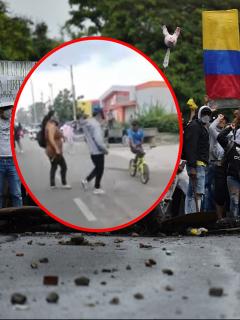 Imagen de mamá sacando a su hijo de protestas y de manifestantes en Colombia