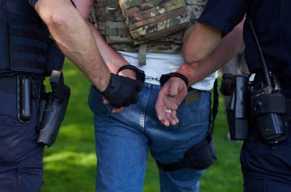 Imagen de hombre esposado ilustra artículo 800 capturas en el mundo luego de que FBI repartiera celulares encriptados