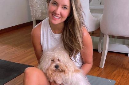 Foto de referencia de Daniela Álvarez con su perro, en nota de su mascota agarrado de pierna del instructor de yoga.