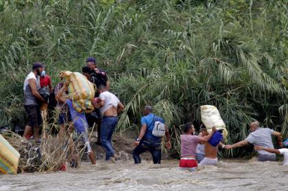 Migrantes venezolanos cruzan el río Táchira a su ingreso a Colombia