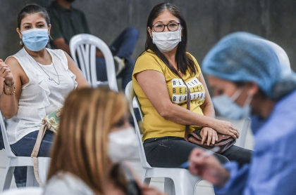 People look as a nurse inoculates a woman against COVID-19 at a vaccination centre mounted at a volleyball arena in which people over 50 are vaccinated amid the ongoing novel coronavirus pandemic, in Medellin, Colombia, on June 1, 2021. (Photo by Joaquin SARMIENTO / AFP)