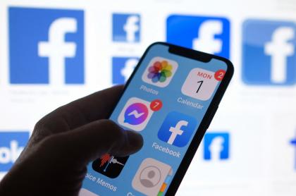 """Imagen de celular sobre logos de Facebook ilustra artículo Facebook lanzó """"audio en directo"""" y pódcast, y desafía a Clubhouse"""
