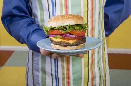Hombre mostrando hamburguesa ilustra los errores comunes al hacer hamburguesas en casa, según el chef Juan Diego Vanegas.