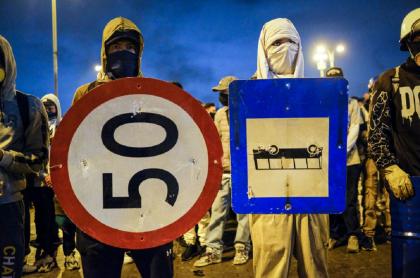 Dos personas usan señales de tránsito como escudos durante las manifestaciones del paro nacional en Bogotá.