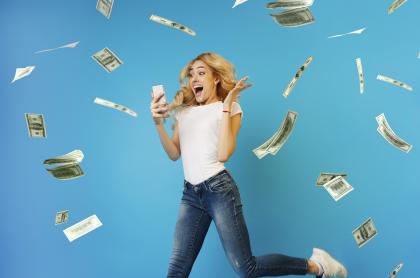 Mujer feliz mirando resultados de juegos de azar con billetes alrededor ilustra qué chance jugó anoche y resultados de Dorado, Sinuano y más de agosto 4 de 2021.