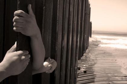 Foto de manos detrás de una cerca, en nota de madre e hija que murieron en frontera de México y Estados Unidos.