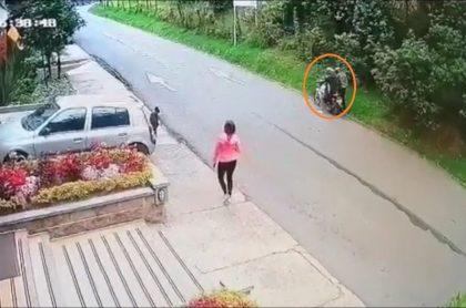Imagen de dos ladrones en moto cuando atacan a una mujer por robarla, en Chapinero