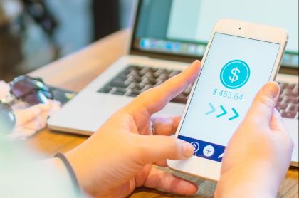 Mujer enviando dinero por 'app' ilustra nota sobre cómo hacer transferencias entre Movii y Nequi