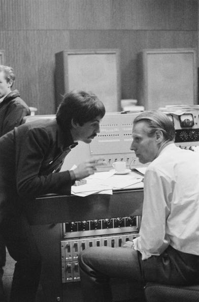 English singer, songwriter and musician Paul McCartney in a studio to record 'The Family Way', November 1966. On the right is arranger and producer George Martin. Composed for the film of the same name, 'The Family Way' is considered by many to be the first Beatles solo album. A photoshoot for The Sunday Times. (Photo by Duffy/Getty Images)