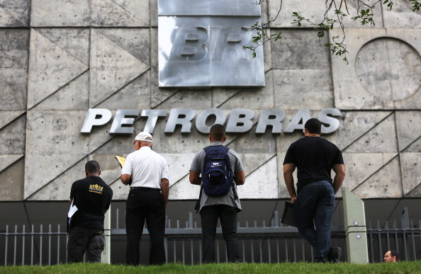 RIO DE JANEIRO, BRAZIL - OCTOBER 18: People stand in front of state oil company Petrobras headquarters after Brazil's oil workers went on strike on October 18, 2013 in Rio de Janeiro, Brazil. Petrobras oil workers are calling for increased pay and for a stop to a planned auction next week of a share of the production rights to the huge offshore Libra oil field. Union leaders say that the about 90 percent of Petrobras' workers are on strike. (Photo by Mario Tama/Getty Images)