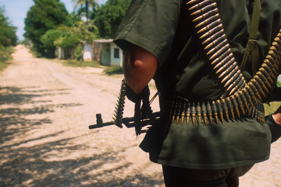 379556 07: (NO NEWSWEEK - NO US NEWS) A Federal Police officer patrols a FARC-controlled, barrio, or slum, August 21, 2000 of Barrancabermeja, Colombia. Barrancabermeja has the highest murder rate of any town in the Western Hemisphere, averaging three murders a day. The FARC and ELN rebels, as well as right-wing paramilitaries fight for control of the area. (Photo by Robert Nickelsberg/Liaison)